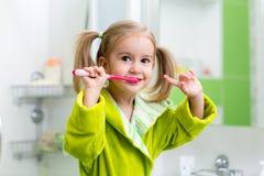 Зубы девушки ребенк чистя щеткой в ванной комнате стоковые изображения rf