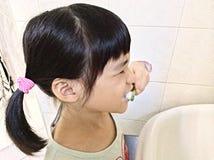 Зубы девушки чистя щеткой истово стоковая фотография