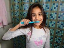 Зубы девушки чистя щеткой Стоковое Изображение