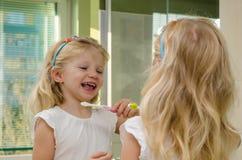 Зубы девушки чистя щеткой Стоковые Изображения