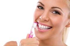 Зубы женщины чистя щеткой держа зубную щетку Стоковые Фото