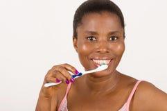 Зубы маленькой девочки чистя щеткой счастливо изолированные на светлой предпосылке стоковое изображение