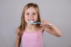 Зубы маленькой красивой белокурой девушки чистя щеткой, здоровая концепция Стоковые Изображения