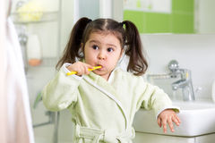 Зубы маленькой девочки ребенка чистя щеткой в ванне Стоковое фото RF