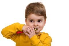 Зубы мальчика чистя щеткой на белой предпосылке Стоковое Изображение RF