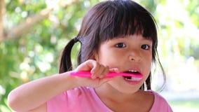 Зубы милой азиатской девушки чистя щеткой акции видеоматериалы