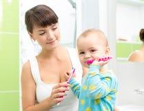 Зубы младенца чистя щеткой в ванной комнате Стоковое Изображение RF