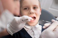 Зубы педиатрического дантиста рассматривая пациента мальчика в зубоврачебной клинике используя зубоврачебные инструменты - зонд и Стоковое Изображение RF