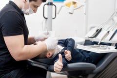 Зубы педиатрического дантиста рассматривая пациента мальчика в зубоврачебной клинике используя зубоврачебные инструменты Пациент  Стоковая Фотография