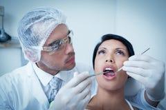 Зубы рассматривая женщины мужского дантиста Стоковая Фотография