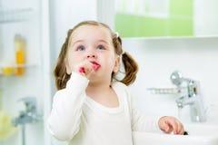 Зубы ребенка чистя щеткой в ванной комнате Стоковое Изображение RF