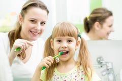 Зубы ребенк чистя щеткой в ванной комнате Стоковое Фото