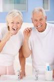Зубы старших пар чистя щеткой стоковые изображения