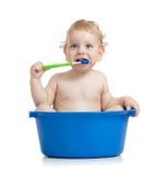 Зубы счастливого малыша младенца чистя щеткой в тазике стоковое изображение