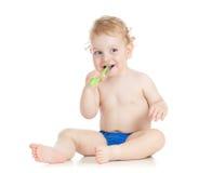 Зубы счастливого ребенка младенца чистя щеткой Стоковые Фото