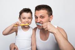 Зубы человека и мальчика чистя щеткой Стоковое Изображение