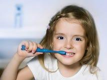 Зубы чистки девушки ребенка с зубной щеткой стоковые изображения rf