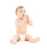 Зубы любознательного младенца чистя щеткой Стоковые Изображения