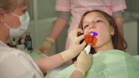 Зуб дантиста светлый заполняя с ультрафиолетовым лучем Завалка зуба Пациент ребенка видеоматериал