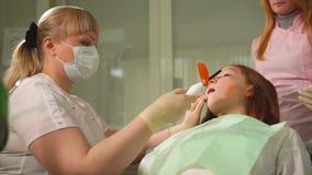 Зуб дантиста светлый заполняя с ультрафиолетовым лучем Завалка зуба Пациент ребенка сток-видео