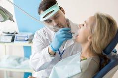 Зуб дантиста сверля клиента стоковое фото