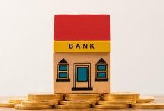 Здание банка игрушки на имуществах золотой монетки Стоковая Фотография