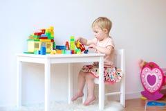 Здание девушки Preschooler от пластичных кирпичей Стоковое фото RF