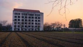 Здание и ферма в заходе солнца Стоковое Изображение RF
