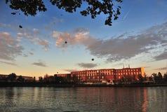 Здание под заходом солнца перед озером Стоковое Изображение