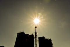 Здание под конструкцией и кран конструкции против неба и солнца Стоковые Фото