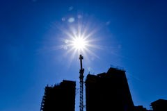 Здание под конструкцией и кран конструкции против неба и солнца Стоковое Фото
