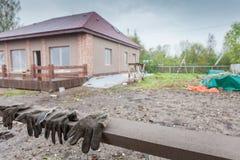 Здание под конструкцией и пакостные работая перчатки на переднем плане Стоковое Фото
