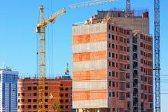 Здание с поднимать краны, краны башни на конструкции здания Стоковое Изображение RF