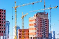 Здание с поднимать краны, краны башни на конструкции здания Стоковые Изображения