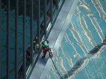 Здание человека очищая стеклянное стоковое фото rf