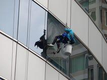 Здание человека очищая стеклянное стоковые фотографии rf