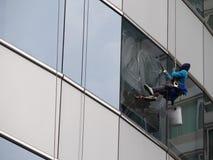 Здание человека очищая стеклянное стоковое фото