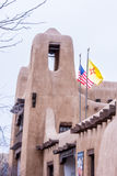 Здание Adobe в Санта-Фе с американцем и флагами Неш-Мексико Стоковые Изображения