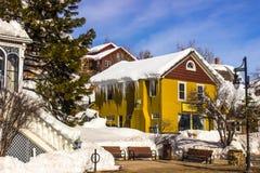 Здания с снегом & сосульки вися от крыши Стоковое Изображение