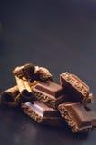 2 здания шоколада на темной предпосылке энергия и сахар Сломленный бар Стог блоков шоколада Стоковые Изображения