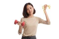Здоровая азиатская бизнес-леди с гантелями и измеряя лентой Стоковое фото RF