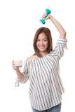 Здоровая азиатская женщина выпивая стекло молока и гантели Стоковое Фото