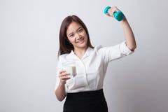 Здоровая азиатская женщина выпивая стекло молока и гантели Стоковое Изображение