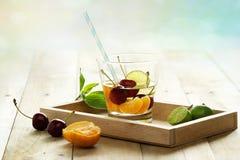 Здоровая вода вытрезвителя, стекло вишни, апельсин и известка на деревянном подносе Стоковая Фотография