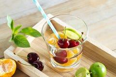 Здоровая вода вытрезвителя, стекло вишни, апельсин и известка на деревянном подносе Стоковые Изображения