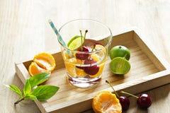 Здоровая вода вытрезвителя, стекло вишни, апельсин и известка на деревянном подносе Стоковые Фотографии RF