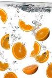 Здоровая вода с свежими апельсинами. Выплеск изолированный на белизне стоковые фото