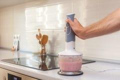 Здоровая еда, варящ, вегетарианская еда Рука человека держит blender ручки погружения Варить milkshake smoothie с бананами и соло Стоковое Изображение