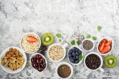 Здоровая еда фитнеса от свежих фруктов, ягод, зеленых цветов, супер еды: kinoa, семена chia, семя льна, клубника, голубика Стоковые Изображения
