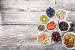 Здоровая еда фитнеса от свежих фруктов, ягод, зеленых цветов, супер еды: kinoa, семена chia, семя льна, клубника, голубика Стоковое Изображение
